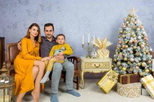 младо семейство с дете седнали на приказен декор от коледна фотосесия софия