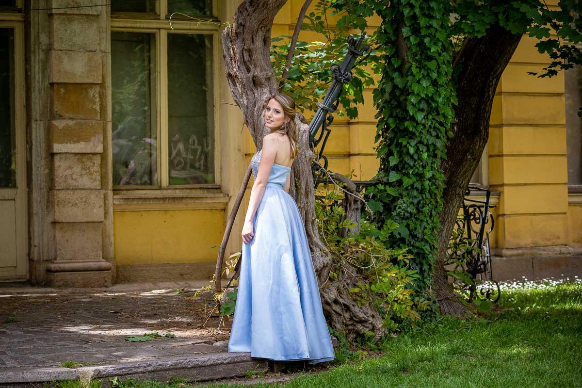 млада дама със синя рокля позира в парка